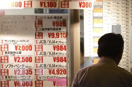 Man looks at prices at ticket shop in Tokyo