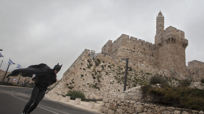 A man on rollerblades in a Batman costume passes the Tower of David during the third annual marathon in Jerusalem, Friday, March 1, 2013. Abraham Kabeto Ketla of Ethiopia has won the third Jerusalem marathon, setting a record for the race. About 20,000 runners took part despite protests by Palestinians. (AP Photo/Sebastian Scheiner)