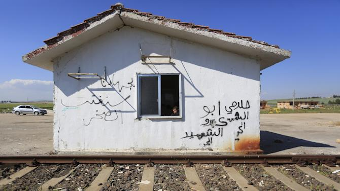 A boy looks out from a window of an abandoned building of Kfar Halab train station in the western countryside of Aleppo