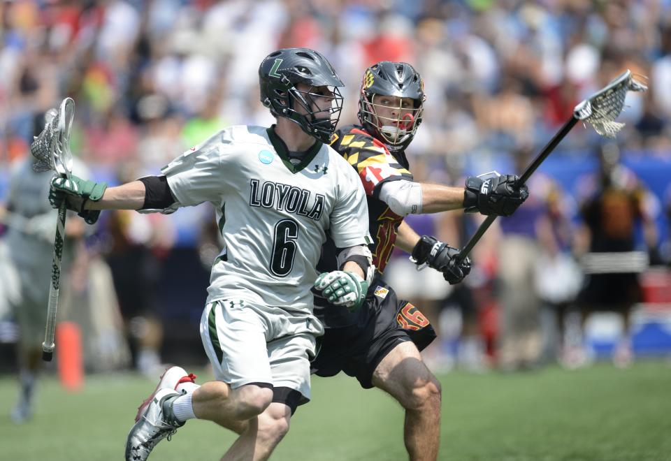 Loyola's Pat Byrnes (6) drives the ball past Maryland's Jesse Bernhardt, right, in the first quarter of their Division I NCAA men's lacrosse championship game at Gillette Stadium in Foxborough, Mass., Monday, May 28, 2012. (AP Photo/Gretchen Ertl)