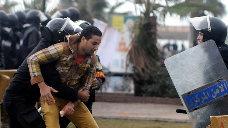 An opponents of Egyptian President Mohammed Morsi is detained by riot police during clashes with Islamist supporters of the president, unseen, in Alexandria, Egypt, Friday, Dec. 21, 2012. Thousands of Islamists clashed with their opponents Friday in Egypt's second largest city, Alexandria, on the eve of the second leg of voting on the country's contentious constitution that has deeply polarized the nation.(AP Photo)
