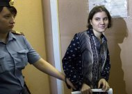 Feminist punk group Pussy Riot member Yekaterina Samutsevich is escorted at a court in Moscow, Russia, Wednesday, Aug. 8, 2012. Prosecutors on Tuesday called for three-year prison sentences for feminist punk rockers who gave an impromptu performance in Moscow's main cathedral to call for an end to Vladimir Putin's rule, in a case that has caused international outrage and split Russian society.(AP Photo/Misha Japaridze)