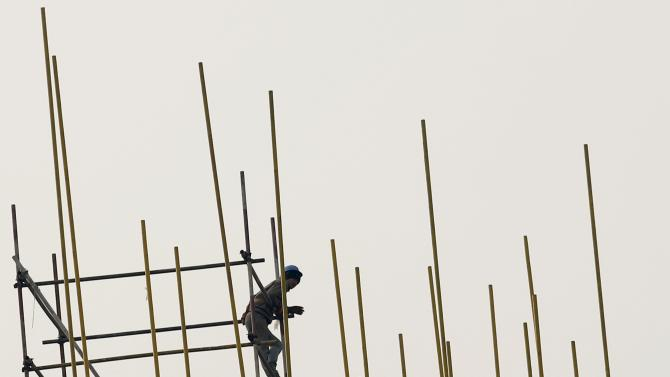 A worker balances on a scaffold at a construction site in Beijing