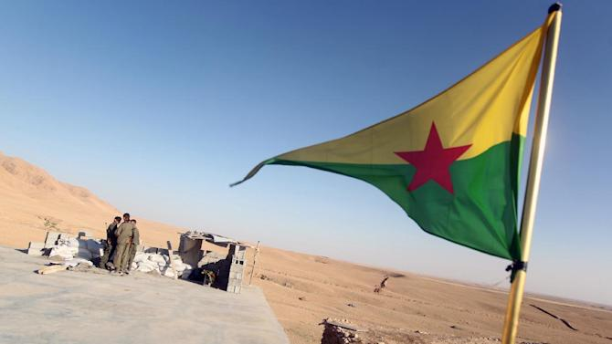 Kurdistan Workers Party (PKK) fighters guard a post flying the PKK flag as they participate in an intensive security deployment against Islamic State group militants in the town of Makhmur on August 21, 2014