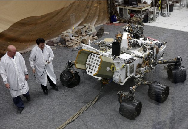 FILE - In this file photo taken Thursday, Aug. 2, 2012, engineers work on a model of the Mars rover Curiosity at the Spacecraft Assembly Facility at NASA's Jet Propulsion Laboratory in Pasadena, Calif