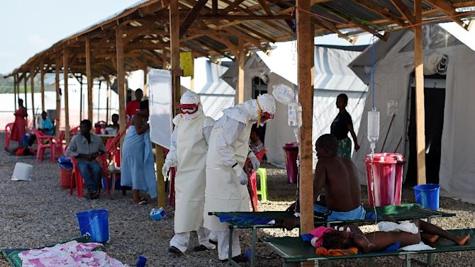 File picture taken on November 15, 2014 shows nurses wearing personal protective equipment  while treating ebola patients at the Kenama treatment center run by the Red Cross Society, in eastern Sierra Leone