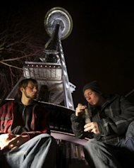 <p>Dustin, left, and Paul of Tacoma, Washington, share a water pip underneath the Space Needle shortly after a law legalizing the recreational use of marijuana took effect on December 6, in Seattle, Washington. Voters approved an initiative to decriminalize the recreational use of marijuana making it one of the first states to do so.</p>
