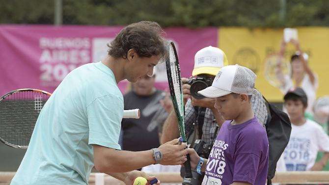 Spanish tennis player Rafael Nadal signs the jersey of a kid of tennis school from a shantytown neighborhood, at San Lorenzo's tennis courts in Buenos Aires, on February 26, 2015