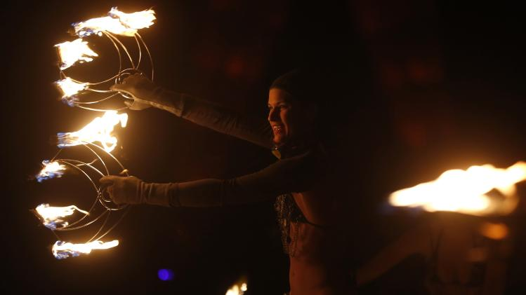 """Members of the Kenna Tribe fire conclave perform before the Man burns during the Burning Man 2014 """"Caravansary"""" arts and music festival in the Black Rock Desert of Nevada"""