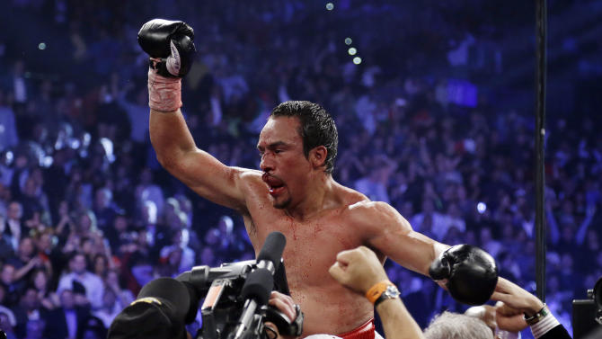 Juan Manuel Marquez, from Mexico, celebrates his sixth round knockout victory over Manny Pacquiao, from the Philippines, in their WBO world welterweight  fight Saturday, Dec. 8, 2012, in Las Vegas.  (AP Photo/Julie Jacobson)