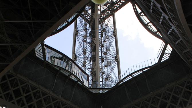 Tourists wander under the Eiffel Tower, in Paris, Friday May 22, 2015. The Eiffel Tower is closed to the public because workers are protesting a recent rise in aggressive pickpockets. The Paris monument is normally open every day of the year and brings in thousands of visitors daily. (AP Photo/Remy de la Mauviniere)