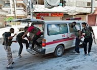 Syrian rebel fighters load a wounded person into an ambulance during clashes with pro-regime forces in the al-Sahur district of Aleppo on August 7. Syria says its troops have seized a rebel-held Aleppo district after storming it and &quot;annihilating&quot; most of the insurgents, as a long-threatened ground assault on the key city was launched