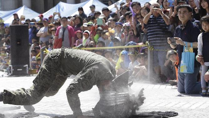 People watch a soldier from the South Korean army special forces break stone plates with his head during a martial arts demonstration for Children's Day at the War Museum in Seoul, Tuesday, May 5, 2015. May 5 is celebrated as Children's Day, a national holiday, in South Korea. (AP Photo/Ahn Young-joon)