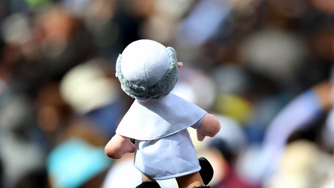 A woman holds a Pope Francis puppet as he arrives at the Catholic University in Quito