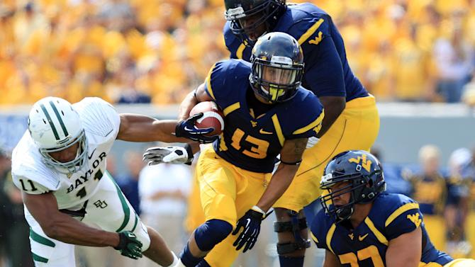 West Virginia running back Andrew Buie (13) breaks a tackle by Baylor's Terrance Lloyd (11) during their NCAA college football game in Morgantown, W.Va., Saturday, Sept. 29, 2012. No. 9 West Virginia beat No. 25 Baylor  70-63.  (AP Photo/Christopher Jackson)
