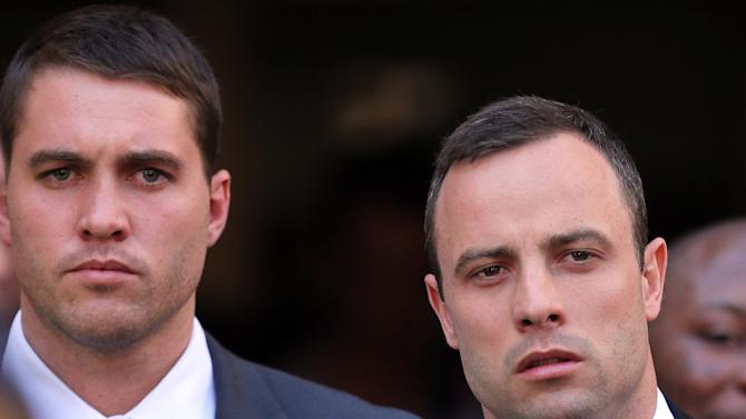 Oscar Pistorius, right, leaves the the high court in Pretoria, South Africa, Thursday, April 10, 2014. Pistorius is charged with murder for the shooting death of his girlfriend, Reeva Steenkamp, on Valentines Day in 2013. (AP Photo/Themba Hadebe)