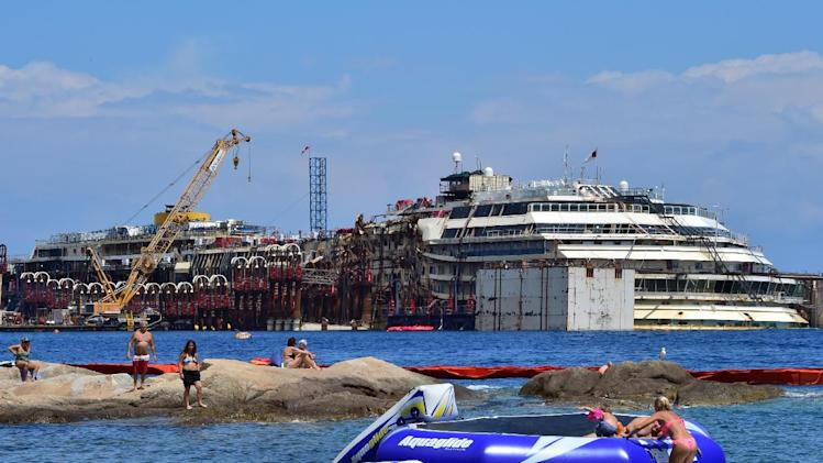 Tourists play in the water at a beach facing the wrecked Costa Concordia cruise ship on July 13, 2014 in Giglio Island
