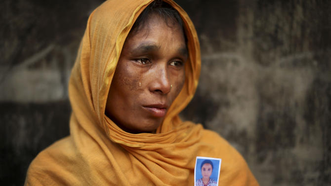 In this Friday, Dec. 21, 2012 photo, Bangladeshi Zamiron Begum, 45, weeps as she displays a photograph of her daughter Bobita Khatum, 18, a senior sewing machine operator who died in the fire at Tazreen Fashions, in the garment district in Ashulia, near Dhaka, Bangladesh. When fire ravaged the Bangladeshi garment factory, killing 112 workers, dozens of their families did not even have a body to bury because their loved ones' remains were burned beyond recognition. Two months later, they have yet to receive any of the compensation they were promised - not even their relatives' last paychecks. The remainder were burnt beyond recognition and their remains are undergoing DNA testing to prevent people from filing fake claims. (AP Photo/Kevin Frayer)