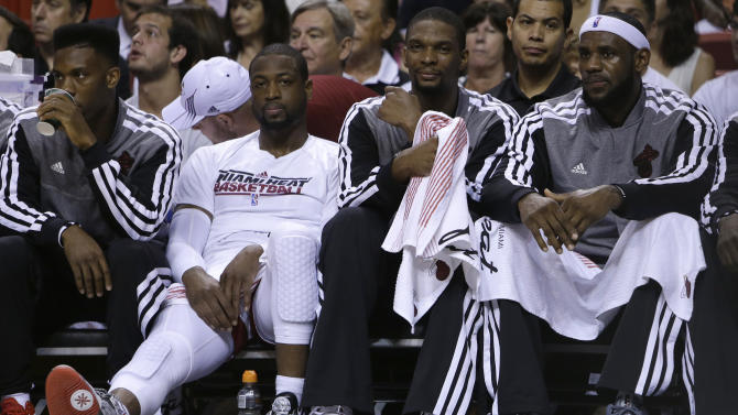 Miami Heat's Norris Cole, left, Dwyane Wade, second from left, Chris Bosh, second from right, and LeBron James, right, watch from the bench during the first half of an NBA basketball game against the Chicago Bulls, Sunday, April 14, 2013, in Miami. (AP Photo/Lynne Sladky)