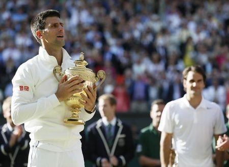 Novak Djokovic of Serbia holds the winner's trophy after defeating Roger Federer of Switzerland in their men's singles finals tennis match on Centre Court at the Wimbledon Tennis Championships in London
