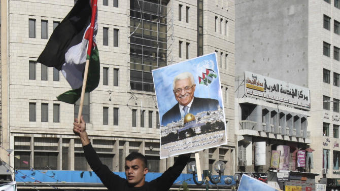 Palestinians hold pictures of President Mahmoud Abbas during a rally supporting the Palestinian UN bid for observer state status, in the West Bank city of Nablus, Thursday, Nov. 29, 2012. The Palestinians are certain to win U.N. recognition as a state on Thursday but success could exact a high price: delaying an independent state of Palestine because of Israel's vehement opposition. (AP Photo/Nasser Ishtayeh)