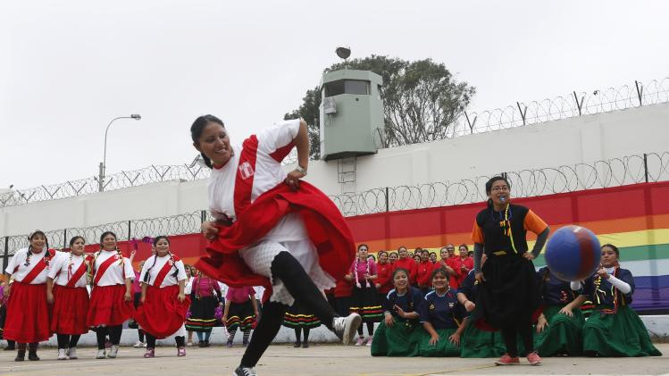 Woman prisoner shoots a penalty during a soccer game before a dance competition inside the Maximum Security prison of Chorrillos in Lima