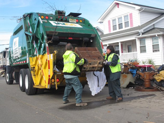 Sanitation workers collect some of the tons of ruined household items from homes in Point Pleasant Beach N.J. on Monday, Nov. 5, 2012. A new storm due Wednesday was raising fears of renewed flooding a