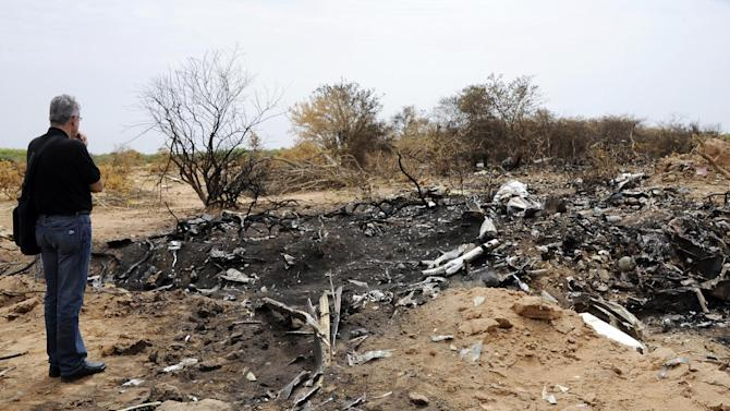 A representative of the Lebanese victims' relatives looks at debris at the crash site of the Air Algerie Flight AH 5017 in Mali's Gossi region, west of Gao, on July 26, 2014