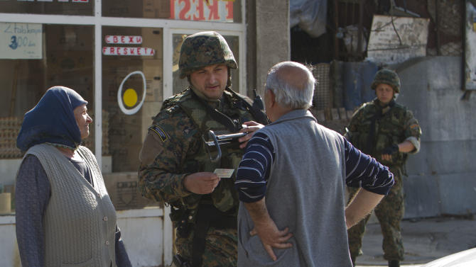 Macedonian special police unit member talks to Albanians leaving the area where a battle took place involving the police and an armed group, in the northern Macedonian town of Kumanovo, on Sunday, May 10, 2015. Fighting between police forces and members of an armed group has ended after two days in the northern Macedonian town of Kumanovo leaving 8 police officers and 14 armed suspected terrorists dead. (AP Photo/Visar Kryeziu)