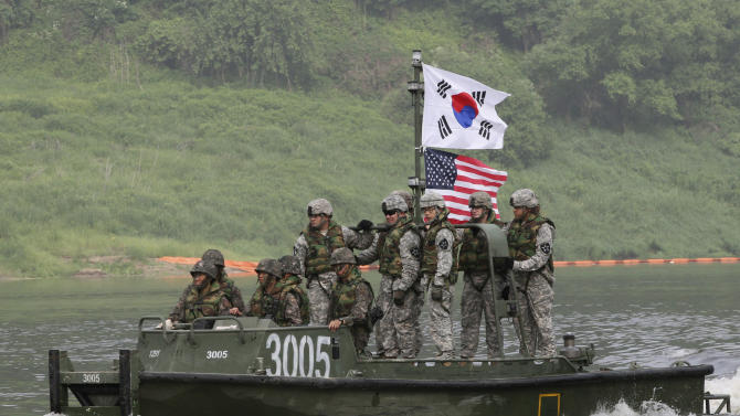 FILE - In this May 30, 2013 file photo, U.S. and South Korean Army soldiers cross Nam Han river during a joint military exercise between the U.S. and South Korea in Yeoncheon near the border with North Korea, in South Korea. North Korea's propaganda machine is churning out near-daily diatribes against the United States and South Korea for a series of soon-to-start military maneuvers, warning nuclear war could be imminent and saying it will take dramatic action of its own if further provoked. (AP Photo/Ahn Young-joon, File)