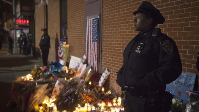 Police stand solemn during a late night vigil at a makeshift memorial at the site where two police officers were shot in the head in the Brooklyn borough of New York