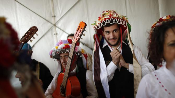 People in traditional costumes look on before competing in the 53rd Verdiales music contest in Malaga