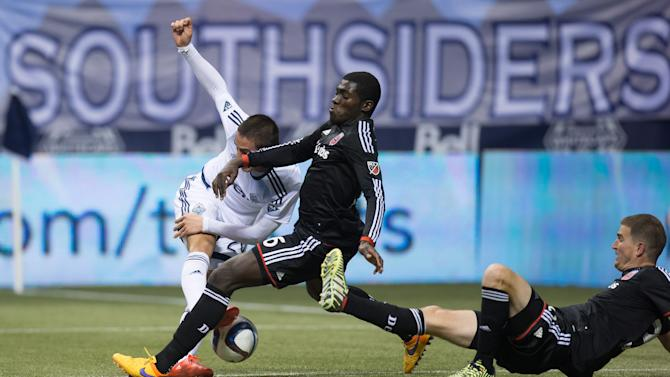 Vancouver Whitecaps' Octavio Rivero, left, of Uruguay, is stopped by D.C. United's Kofi Opare, center, of Ghana, as United's Bobby Boswell, right, falls dduring the second half of an MLS soccer game Saturday, April 25, 2015, in Vancouver, British Columbia. (Darryl Dyck/The Canadian Press via AP)