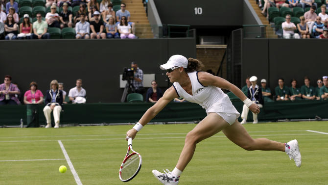 Samantha Stosur of Australia returns a shot to Carla Suarez Navarro of Spain during a first round match at the All England Lawn Tennis Championships at Wimbledon, England, Monday, June 25, 2012. (AP Photo/Alastair Grant)