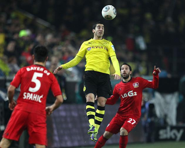 Dortmund's Henrikh Mkhitaryan, center, and Leverkusen's Gonzalo Castro, right, challenge for the ball during the German first division Bundesliga soccer match between Borussia Dortmund and Bay