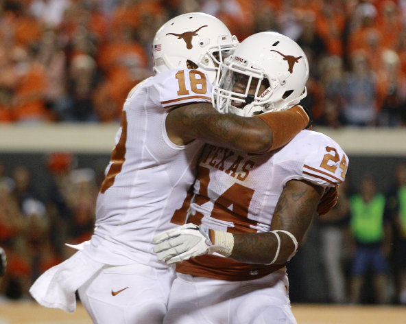 Texas right end D.J. Grant (18) and running back Joe Bergeron (24) celebrate Bergeron&#39;s touchdown against Oklahoma State in the fourth quarter of an NCAA college football game in Stillwater, Okla., Saturday, Sept. 29, 2012. Texas won 41-36. (AP Photo/Sue Ogrocki)