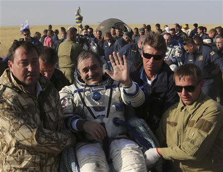 Russia's space agency ground personnel carry Soyuz spacecraft crew after landing near the town of Zhezkazgan