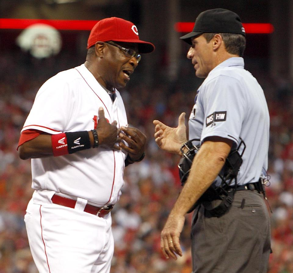 Cincinnati Reds manager Dusty Baker, left, has words with home plate umpire Angel Hernandez, right, after Reds' Devin Mesoraco was called out on a batter's interference to the catcher in the second inning of a baseball game, Sunday, June 10, 2012, in Cincinnati. (AP Photo/David Kohl)