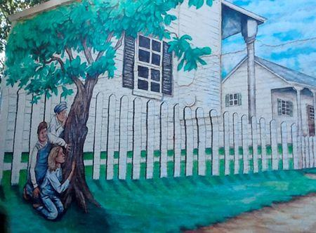 A hand-painted mural is shown on a building near where the Lee and Capote house stood in Monroeville