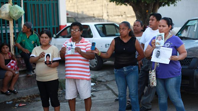 People hold portraits of their missing loved ones in front of the morgue of Cosamaloapan, with the hope of finding and identifying the bodies of their missing, from a mass grave which has been recently discovered, in Veracruz , Mexico, Wednesday, June 18, 2014. At least 28 bodies have been recovered from the mass grave in Veracruz, an eastern Mexican state plagued by attacks on migrants and drug cartel violence, officials said Wednesday. (AP Photo/Felix Marquez)