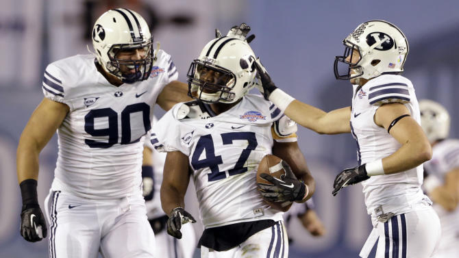 BYU linebacker Ezekiel Ansah, center, is congratulated by Bronson Kaufusi, left, and Daniel Sorensen after intercepting a San Diego State pass during the first half of the Poinsettia Bowl NCAA college football game, Thursday, Dec. 20, 2012, in San Diego. (AP Photo/Lenny Ignelzi)