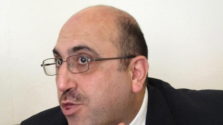 In this photo taken on Wednesday, Oct. 10, 2013, Rami Abdurrahman, gestures during an interview with The Associated Press in Coventry, England. He's practically a one man band, but Rami Abdurrahman's influence extends far beyond his modest home in this small English city. The bald, bespectacled 42-year-old operates the Syrian Observatory for Human Rights from his house in the cathedral city of Coventry — and a review of recent media coverage suggests its running tally of killings and clashes is the most frequently cited individual source of information on Syria's civil war for the world's leading news organizations. (AP Photo/Raphael Satter)