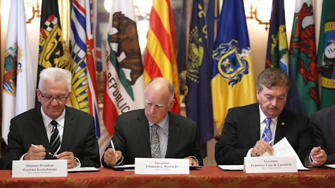 FILE -- In this May 19, 2015 file photo, Gov. Jerry Brown, center, flanked by Baden-Wurttemberg Minister-President Winfried Kretschmann, left, of Germany, and Baja California Gov. Francisco A. Vega de Lamadrid, join others in signing a non-binding climate change agreement in Sacramento, Calif. Brown will travel to the U.N. Climate Change conference to promote California's efforts to curb greenhouse gas emission and urge other governments to sign on to his climate pact.(AP Photo/Rich Pedroncelli, file)