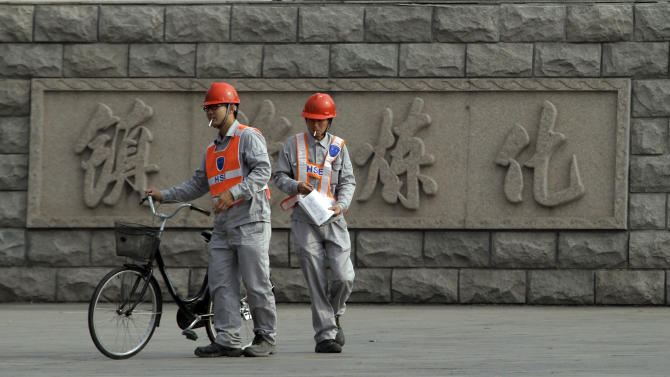 Chinese workers pass by the Chinese characters for Zhenhai refinery outside the Sinopec Zhenhai petrochemical factory where an expansion was proposed on the outskirts of Ningbo city in eastern China's Zhejiang province Monday, Oct. 29, 2012. After three days of protests by thousands of citizens over pollution fears, a local Chinese government relented and agreed that the petrochemical factory would not be expanded, only to see the protests persist. (AP Photo/Ng Han Guan)