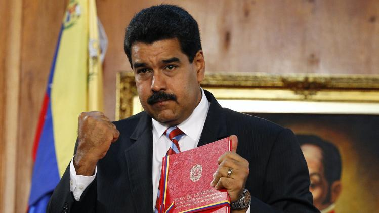 "Venezuelan President Maduro holds a document approving a new law called ""The Fatherland Project"" at Miraflores Palace in Caracas"