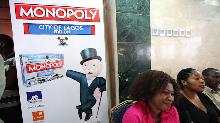 People sit near a banner during the presentation of a Lagos-themed Monopoly board game in Lagos, Nigeria, Tuesday, Dec. 11, 2012. Nigeria's largest city of Lagos is no boardwalk, but now Monopoly is taking an inspiration from the sprawling chaos.  (AP Photo / Sunday Alamba )
