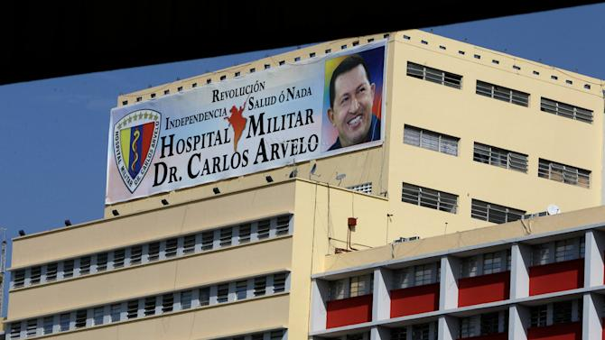 A banner bearing a photo of Venezuela's President Hugo Chavez is displayed on a building of the Carlos Arvelo Military Hospital in Caracas, where the ailing leader is expected to continue his treatment, in Caracas, Venezuela, Monday, Feb. 18, 2013.  Chavez returned to Venezuela early Monday after more than two months of medical treatment in Cuba following cancer surgery, and was being treated at the Caracas' military hospital, his government said. (AP Photo/Fernando Llano)