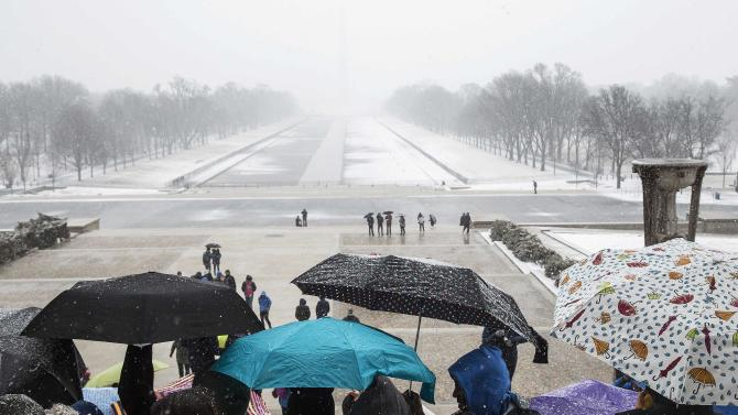 Tourists take shelter under umbrellas at the Lincoln Memorial during a snow storm in Washington