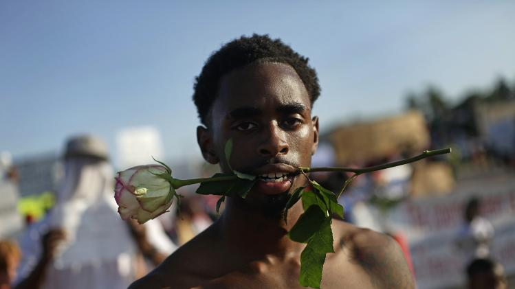 A demonstrator protesting against the fatal shooting of Michael Brown holds a rose in his mouth in Ferguson