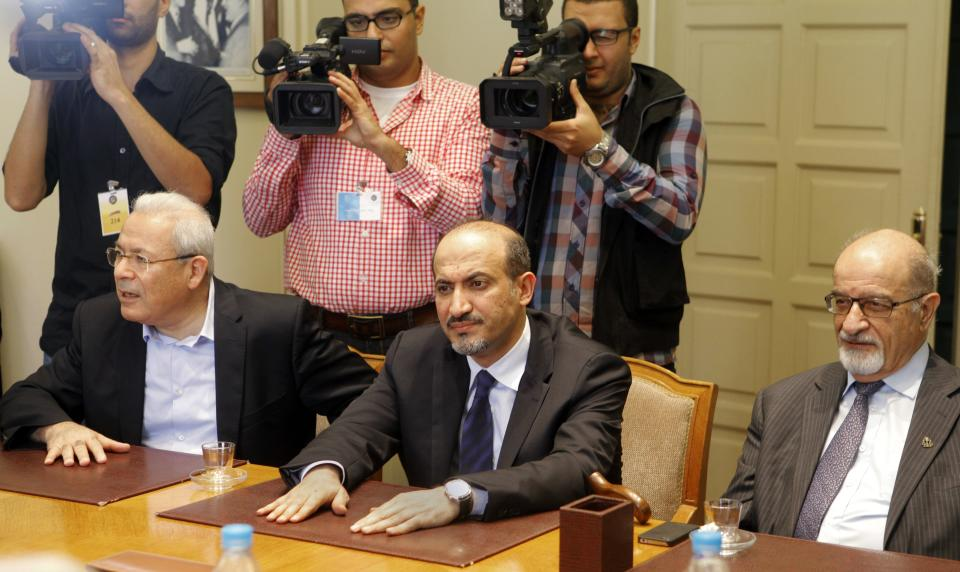 Cameramen film a meeting between the opposition Syrian National Coalition headed by Ahmad Jarba, center, and Arab League General Secretary Nabil al-Arabi, not pictured, at the Arab league headquarters in Cairo, Egypt, Saturday, Nov. 2, 2013. (AP Photo/Amr Nabil)